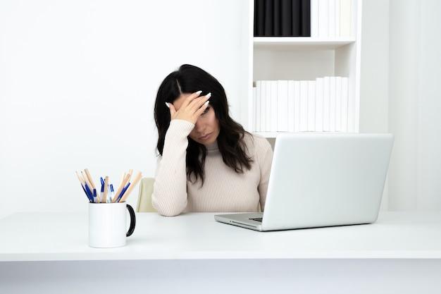 Verdrietig en moe zakenvrouw werken aan de balie op de computer. hoofdpijn begrip.