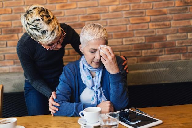 Verdrietig en ongelukkig senior moeder zittend in café-bar of restaurant met haar dochter van middelbare leeftijd en praten.