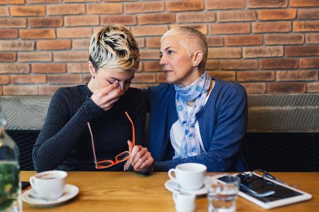 Verdrietig en ongelukkige dochter zit in café-bar of restaurant met haar moeder en praat.