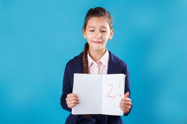 Verdrietig gestresst studentenmeisje dat slechte resultaten van onderzoek in haar notitieboekje toont
