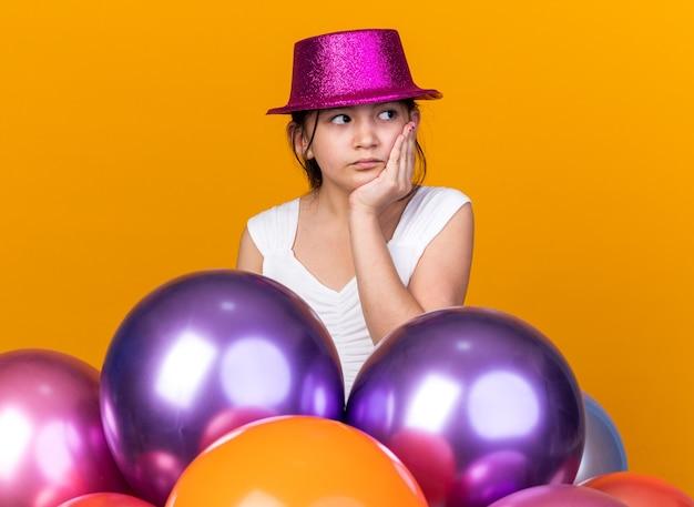 Verdrietig jong kaukasisch meisje met paarse feestmuts die hand op het gezicht zet en naar de zijkant kijkt met heliumballonnen geïsoleerd op een oranje muur met kopieerruimte