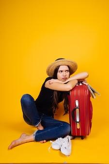 Verdrietig jong meisje gaat op reis, op vakantie, zittend naast een grote koffer