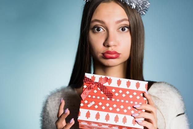 Verdrietig jong meisje viert het nieuwe jaar, houdt een geschenkdoos vast