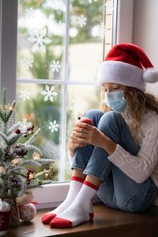 Verdrietig kind blijft in de kersttijd thuis. wintervakantie tijdens pandemisch coronavirus covid 19-concept
