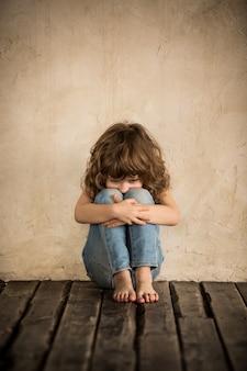 Verdrietig kind dat op de vloer zit in een donkere kamer