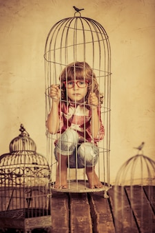 Verdrietig kind in stalen kooi. mensenrechten concept