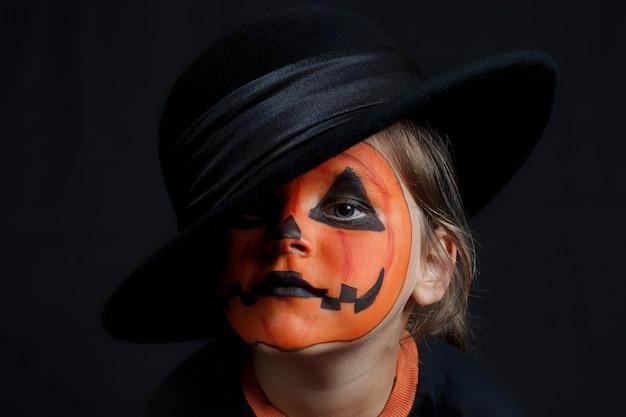 Verdrietig kind met een pompoenpatroon op zijn gezicht in de zwarte hoed, halloween en ziet eruit als een joker