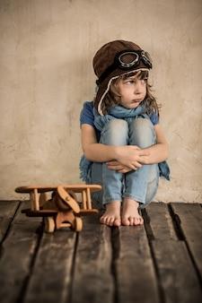 Verdrietig kind met speelgoed houten vliegtuig zittend op de vloer