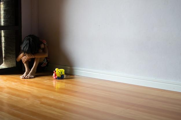 Verdrietig kinderen, meisje alleen zitten in de hoek thuis