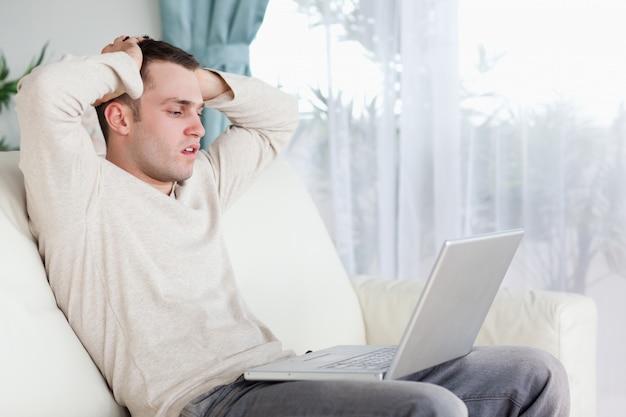 Verdrietig man aan het werk met zijn laptop