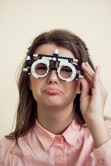 Verdrietig meisje heeft oogproblemen. portret van boos sombere europese vrouw in oogarts kantoor, visie testen zittend en dragen phoropter, betreurend dat ze zicht in de buurt van computer bedorven