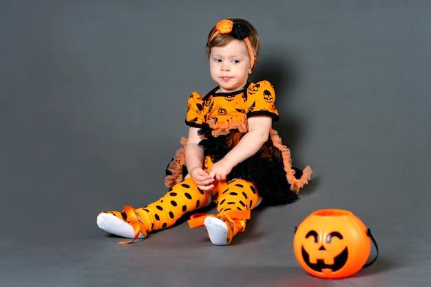 Verdrietig meisje in halloween kostuum kind kijken naar een jack pompoen snoep kom voor een vakantie in een d...