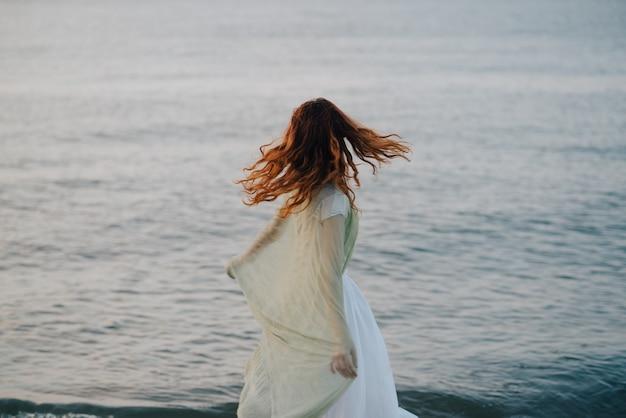 Verdrietig meisje in lange jurk aan zee
