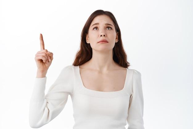Verdrietig meisje kijkt op met spijt en teleurstelling, wijst met de vinger opzij op de bovenste banner, verlangt naar iets, wil iets voor zichzelf hebben, staande tegen een witte muur