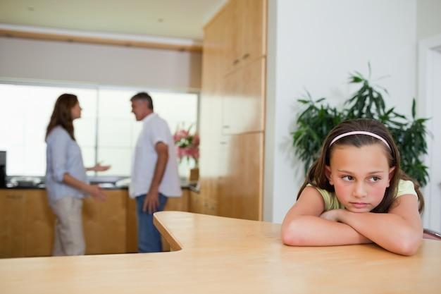 Verdrietig meisje luistert naar vechtende ouders