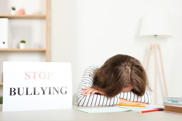 Verdrietig meisje met een stop pesten teken
