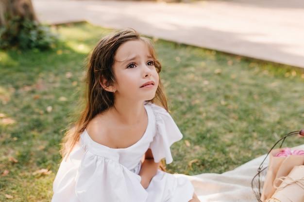 Verdrietig meisje met lichtbruin haar staat op het punt te huilen, zittend op een deken naast een steegje. outdoor portret van ongelukkig kind opzoeken met ogen vol tranen in park.
