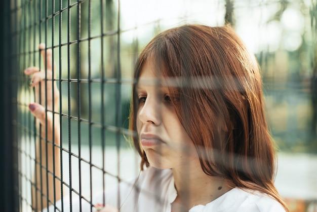 Verdrietig meisje staat aan de bars, concept van verboden en beperkingen