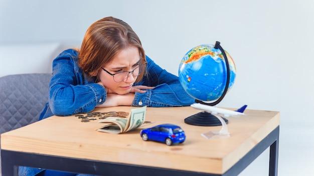 Verdrietig meisje telt haar spaargeld en droomt over reizen en eigen voertuigen. concept van spaargeld.