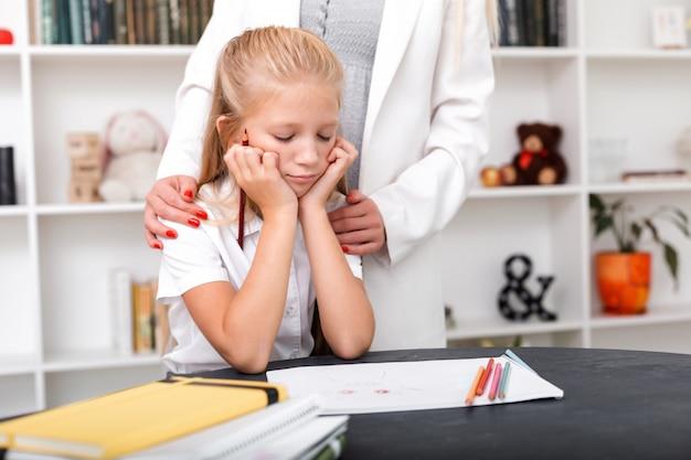 Verdrietig meisje zit aan de tafel, trekt, haar moeder knuffelt haar schouders en troost