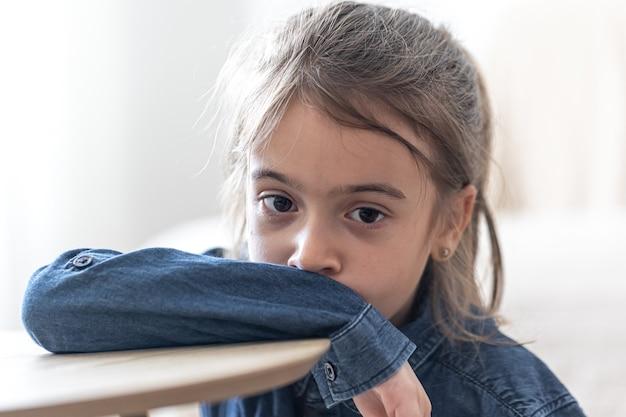 Verdrietig meisje zittend aan de tafel op school, terug naar school concept.