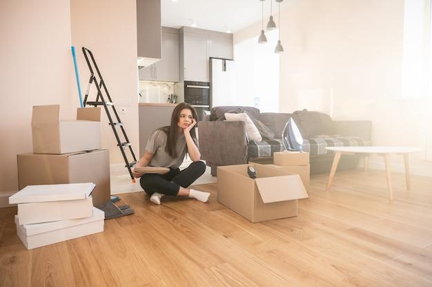 Verdrietig meisje zittend op de vloer en borden thuis te houden. jonge mooie europese vrouw. kartonnen dozen met dingen. concept van verhuizen in nieuwe flat. interieur van studio-appartement. zonnige dag