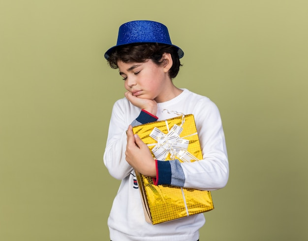 Verdrietig met gesloten ogen kleine jongen met een blauwe feesthoed met een geschenkdoos geïsoleerd op een olijfgroene muur