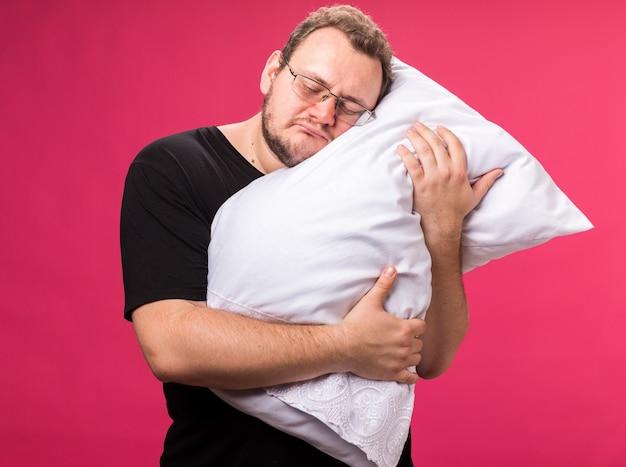 Verdrietig met gesloten ogen zieke man van middelbare leeftijd omhelsde kussen geïsoleerd op roze muur