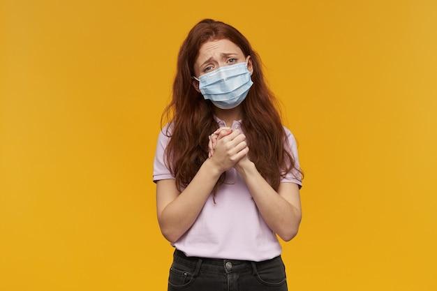 Verdrietig, overstuur jonge vrouw die een medisch beschermend masker draagt, houdt de handen in gebedshouding en bedelt over de gele muur