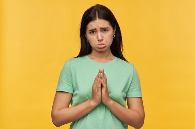 Verdrietig, overstuur jonge vrouw met donker haar in mint tshirt houdt handen in biddende positie en vraagt om hulp over gele muur