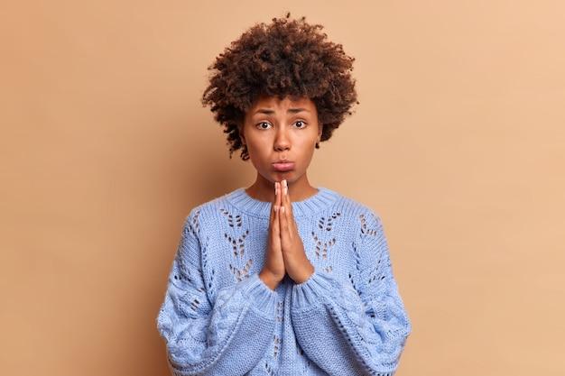 Verdrietige jonge vrouw vraagt om vergeving houdt handpalmen tegen elkaar moet zich verontschuldigen met een droevige gezichtsuitdrukking heeft onschuldige blik maakt smeekbede bidgebaar heeft iets nodig