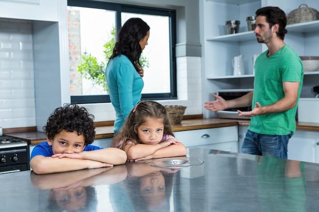 Verdrietige kinderen die luisteren naar het argument van de ouders