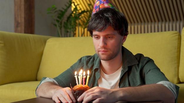 Verdrietige man viert zijn verjaardag alleen in de woonkamer, terwijl hij de kaarsjes op de taart uitblaast