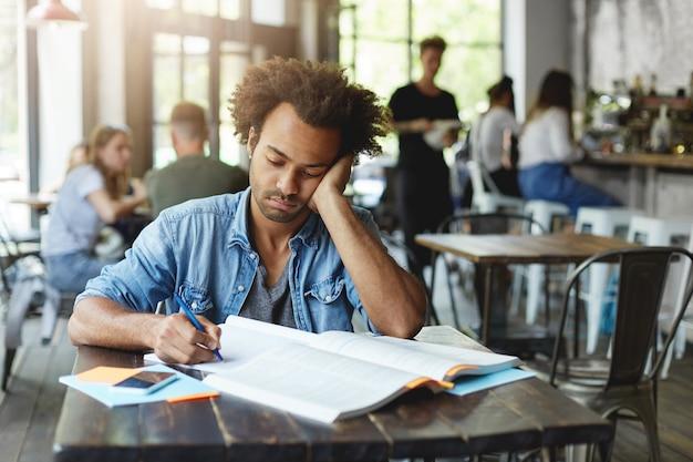 Verdrietige, ongelukkige, donkere, bebaarde student die zich gefrustreerd voelt terwijl hij zich voorbereidt op lessen op de universiteit, met pen in zijn schrift opschrijft, op zijn elleboog leunt en met een verstoorde uitdrukking naar aantekeningen kijkt