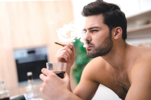 Verdrietige vent die alleen rookt en drinkt