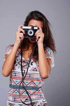 Verduisterd gezicht met een retro camera