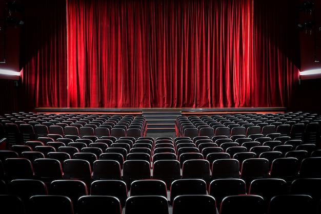Verduisterde lege bioscoop en toneel met de rode gordijnen dicht, bekeken over rijen lege stoelen van achteren