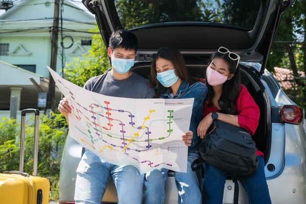 Verdwaald geraken. groep aziatische vrienden met gezichtsmasker zitten op de achterkoffer van suv-auto om de reiskaart te controleren. jonge man en vrouw hebben een roadtrip vakantie vakantie. reislocatie vinden.