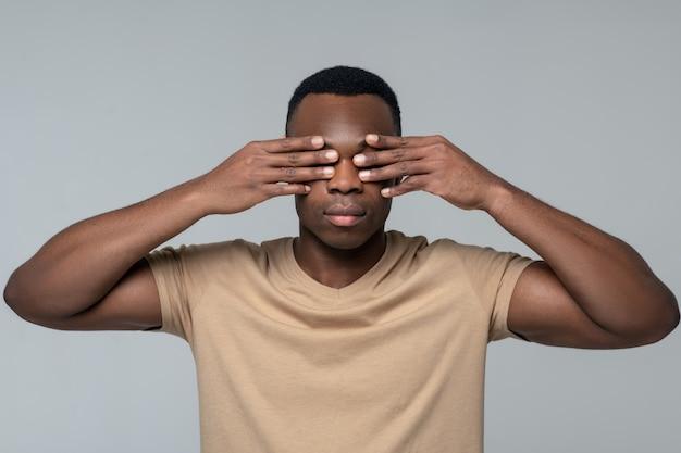 Verdwijning. jonge volwassen zwarte man die betrekking hebben op ogen met handen kalm staande op lichte achtergrond in de studio