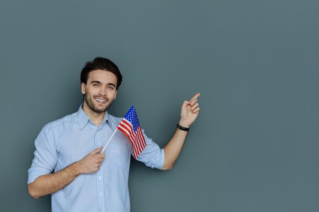 Verenigde staten van amerika. vrolijke gelukkige positieve man glimlachend en wijzend met zijn hand terwijl hij de verenigde staten van amerika laat zien