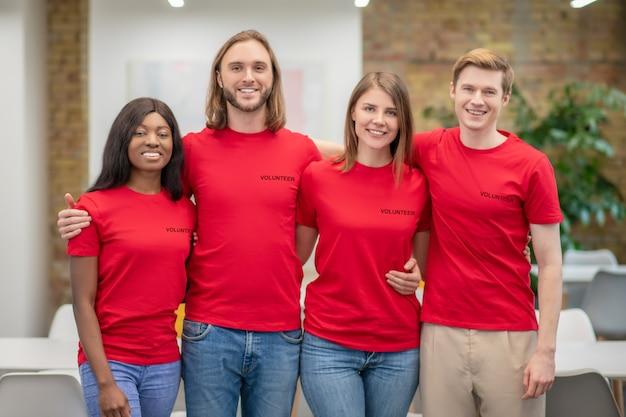 Vereniging, initiatief. groep lachende jonge mensen vrijwilligers in rode t-shirts permanent knuffelen in uitstekende sfeer binnenshuis