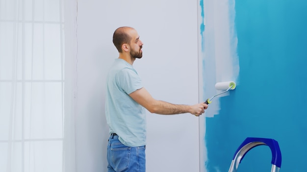 Verf de muur van het appartement opnieuw met witte verf met een rolborstel. renovatie van het huis. klusjesman aan het renoveren. appartement herinrichting en woningbouw tijdens renovatie en verbetering. reparatie en decoreren.