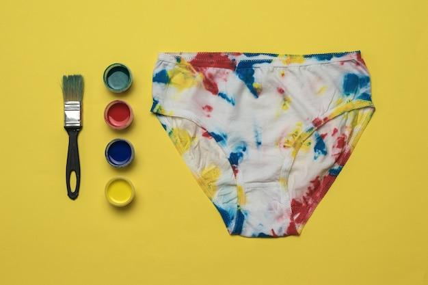 Verf en beschilderde damesslipjes in de stijl van tie-dye op een gele achtergrond. gekleurd ondergoed in huis.