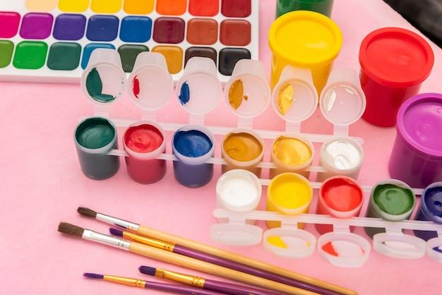 Verf en palet op een roze achtergrond met penselen.