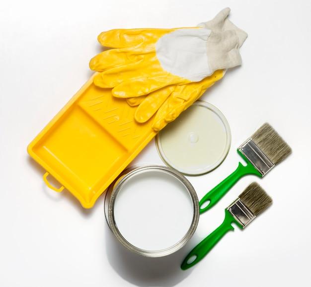 Verf in een ijzeren pot, verfbak en borstels met gele handschoenen op een witte achtergrond.