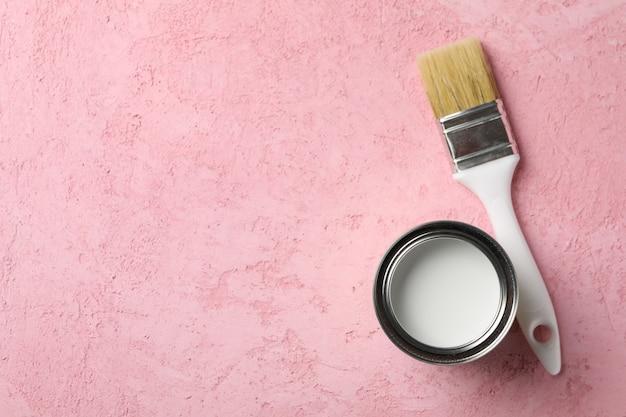 Verf kan en penseel op roze achtergrond, bovenaanzicht