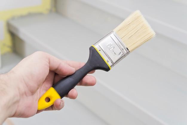 Verf penseel in de hand, het aanbrengen van verf op een houten oppervlak tijdens reparatie