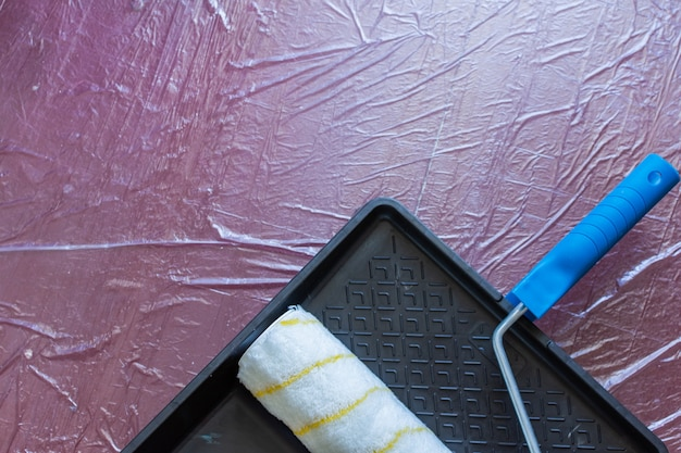 Verfbak en roller op de vloer bedekt met tafelzeil