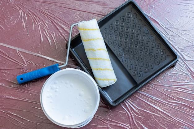 Verfbak met roller en een blik witte verf op de vloer, de vloer is bedekt met een tafelzeil ter bescherming