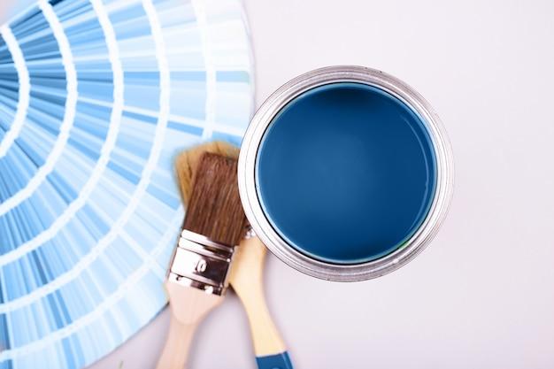 Verfborstel die op hoop van kleursteekproeven legt. open blikje blauwe verf